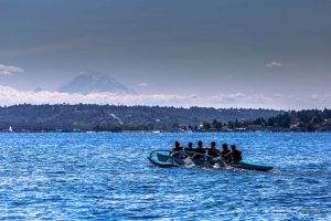Men paddling outrigger canoe with Mt. Rainier in the background